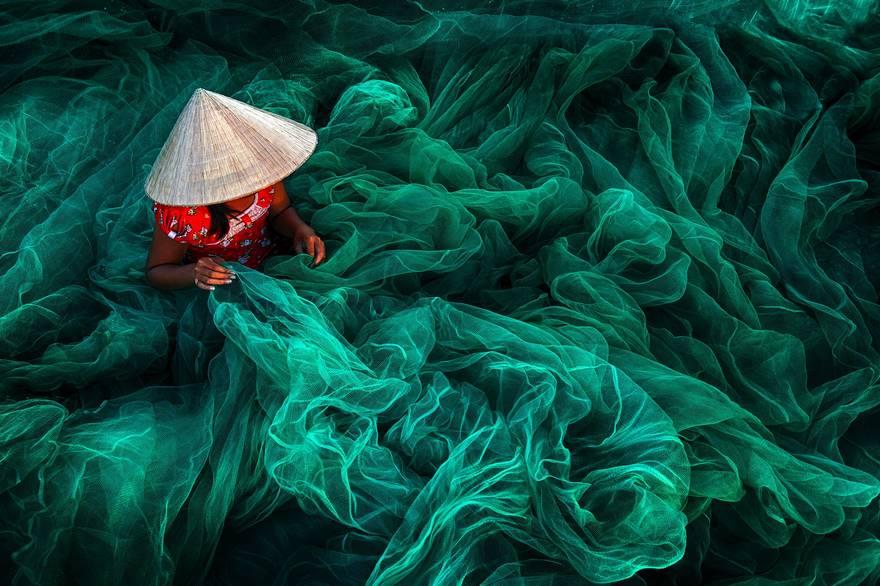 Женщина плетет рыболовную сеть. Небольшая деревня на юге Вьетнама.