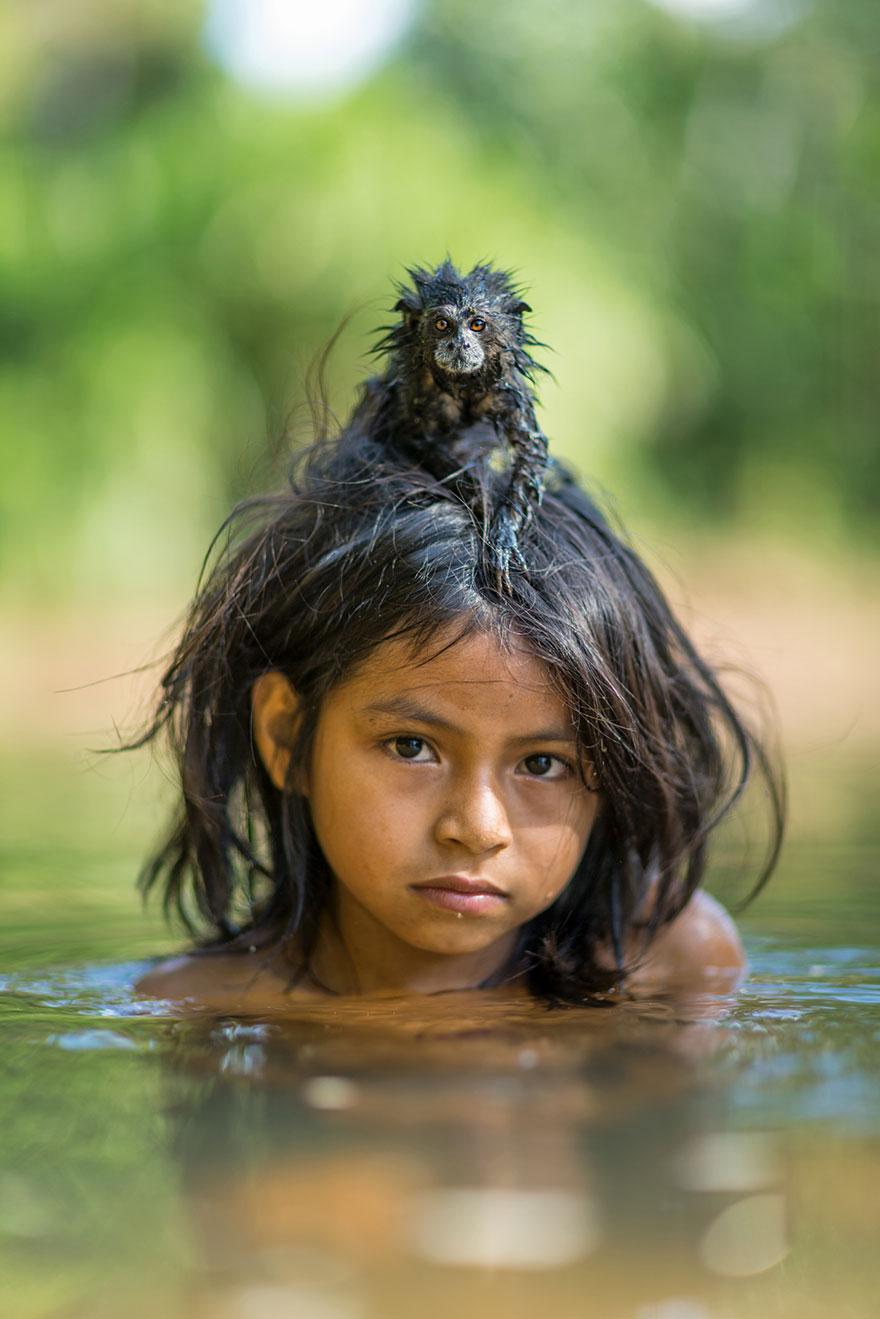 Буроголовый тамарин сидит на голове своей маленькой хозяйки из индейского племени мачигенга. Берег реки Йомбиато, национальный парк Ману в Перу. Фото: CHARLIE HAMILTON JAMES, boredpanda.com