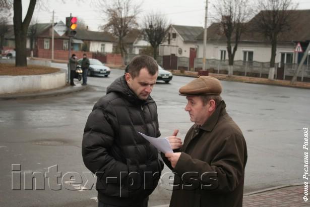 Мясцовы сход. Віктар Сырыца паказвае супрацоўніку міліцыі адказ, які атрымаў з урада, 2011 год.