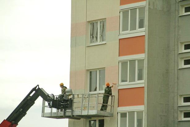 Строители спустя месяц после сдачи социального дома в Барановичах в эксплуатацию завершают внешнюю отделку дома. Фото Intex-press