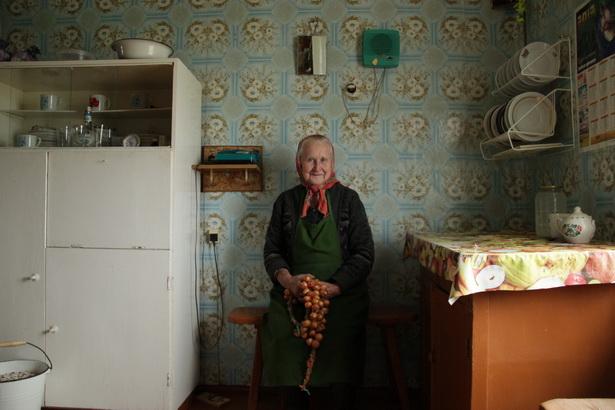 Лёня Данількевіч, якой 82 гады, у кухні сваёй хаты з цыбуляй, якую пасадзіла і сабрала ўласнымі рукамі.
