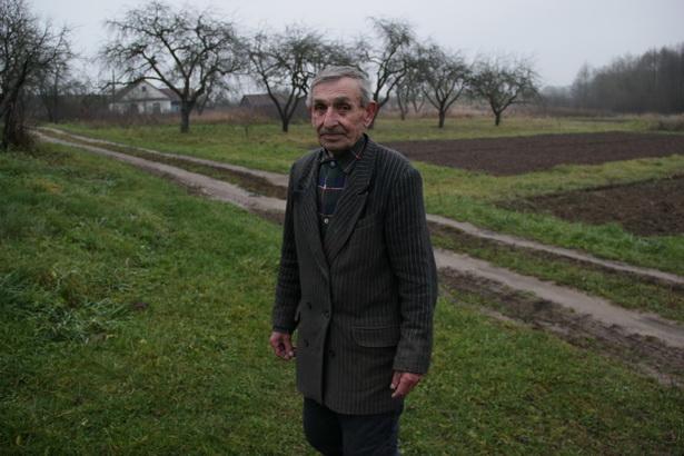 Анатоль Маруцік, якому 79 гадоў, каля вясковай дарогі, што падзяляе вёску на дзве часткі.