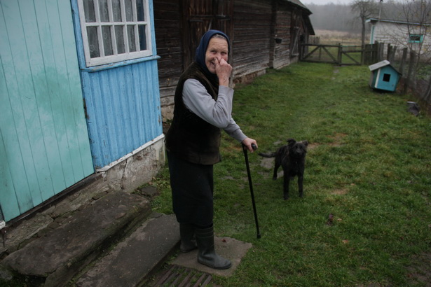 Феня Пракопчык, якой 83 гады, са сваім сабакам на панадворку.