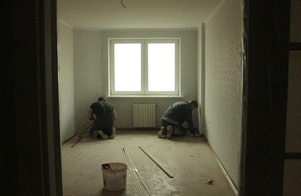 Отделочники устанавливают плинтуса в квартирах