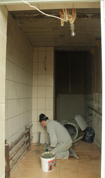 Строители занимаются отделкой мусороприемника.