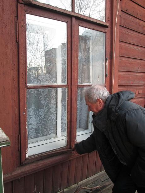 Юрий Дребезов говорит, что каждый год меняет стекла, потому что из-за усадки здания они постоянно лопаются. Несмотря на неудобства, он считает, что свое жилье все равно лучше, чем арендованное. Фото: Татьяна НЕКРАШЕВИЧ.