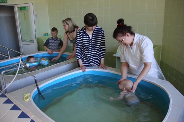 Инструктор ЛФК бассейна детской поликлиники Любовь Ковальчук знакомит маму с основными упражнениями в воде