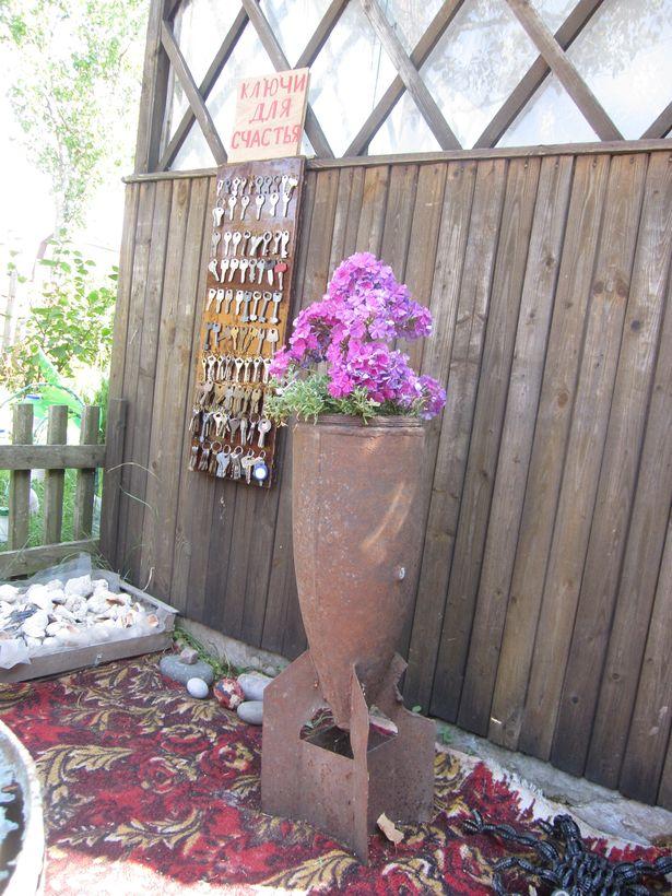 Найденный на участке снаряд Людмила украсила цветами и преобразовала в вазон.