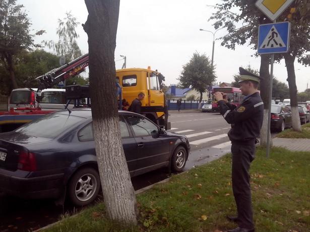 Прежде чем эвакуировать авто, сотрудник ГАИ фотографирует его. фото Натальи Семенович