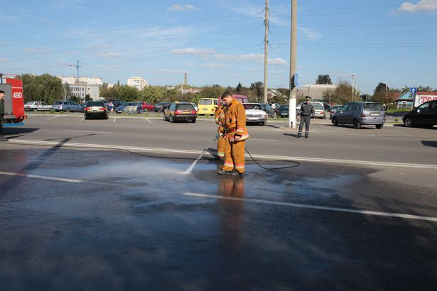 Сотрудники МЧС смывают масло с места аварии