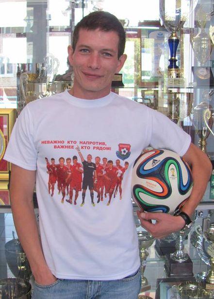 Владимир Мартыненко, сотрудник ЧСУП Футболономик, демонстрирует футболку с атрибутикой клуба. Фото : ЧСУП Футболономик.