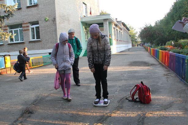 Учащаяся 4-го класса Анжела Котик взвешивается во дворе школы. Вес ее портфеля оказался тяжелее нормы почти на килограмм. Фото: Александр ТРИПУТЬКО