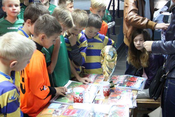 Дети рассматривают сувениры с атрибутикой футбольного клуба.Фото: Александр Трипутько.