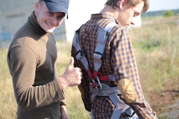 Евгений закрепляет снаряжение перед первым прыжком Олега.