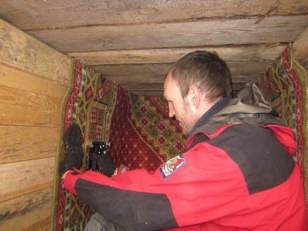 Владимир Кексин обшивает будку старым ковром. Фото: Ольга ШИРОКОСТУП
