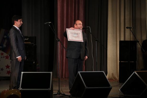 Председатель Барановичского горисполкома Юрий Громаковский вручает подарочный сертификат