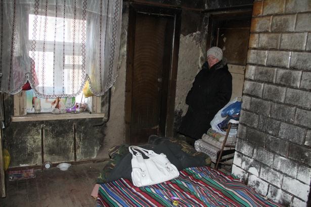 Женщина спит в кухне, только в этой части дома сохранилась крыша. Печка давно не работает, и в помещении так же холодно, как и на улице. Фото: Александр ТРИПУТЬКО