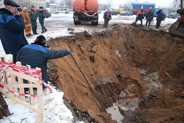 Работники Водоканала измеряют глубину ямы. Фото: Дмитрий МАКАРЕВИЧ.