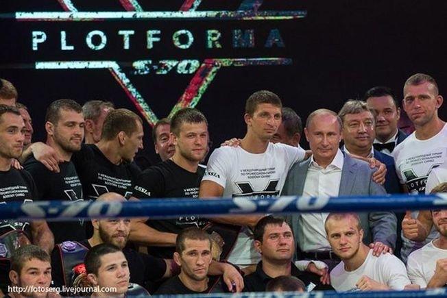 Расул — в нижнем ряду, в белой майке. На его плече — левая рука Путина.