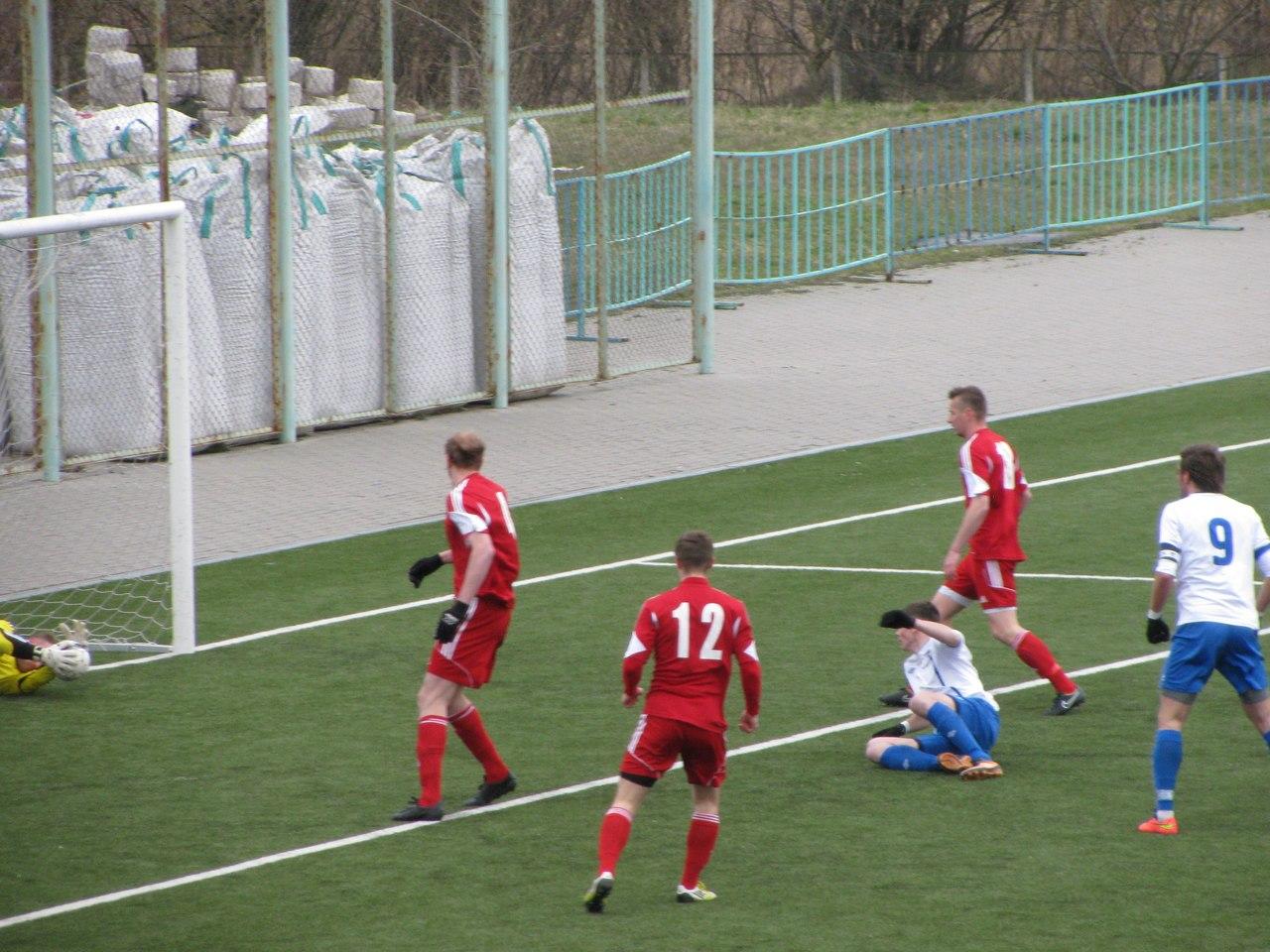 Дмитрий Тарасевич (слева) зафиксировал мяч после удара Юрия Мархеля (сидит на газоне). Фото: Дмитрий КУЗНЕЦОВ
