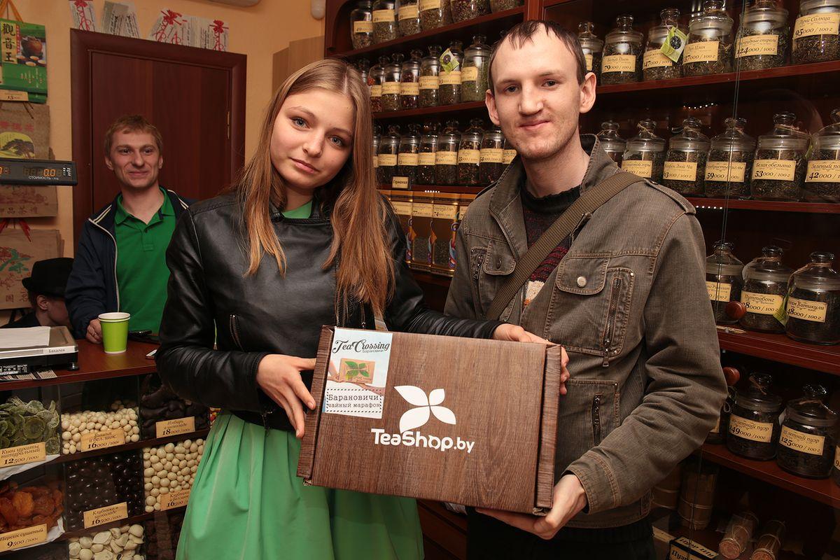 Первая участница акции в Барановичах Алеся Абрамова получила коробку от инициаторов чайного марафона Владимира Кексина (справа) и владельца чайного магазина Вадима Клишевского.