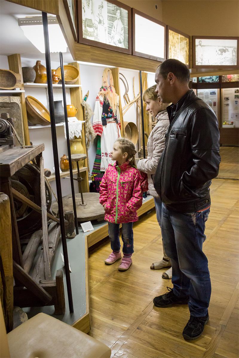 Виктор, Наталья и Машенька с интересом рассматривают экспонаты музея