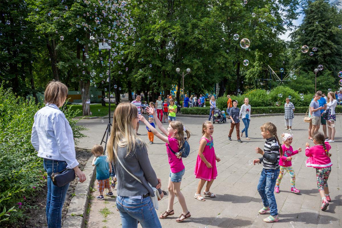 Вокруг генератора мыльных пузырей веселятся дети
