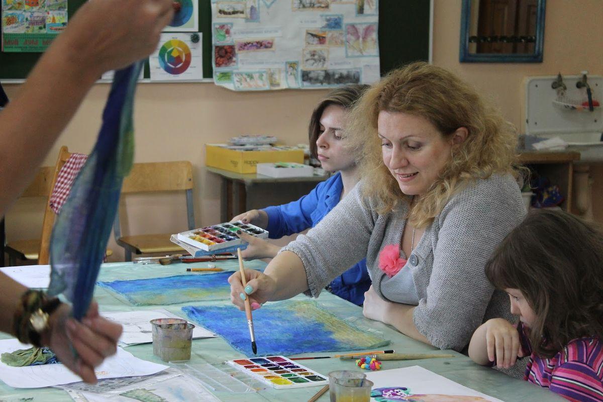 Татьяна Можейко под наблюдательным взглядом своей дочери Агнии на марле поверх листа бумаги рисует фон для будущей картины. Фото: Катя ГЕТЦ