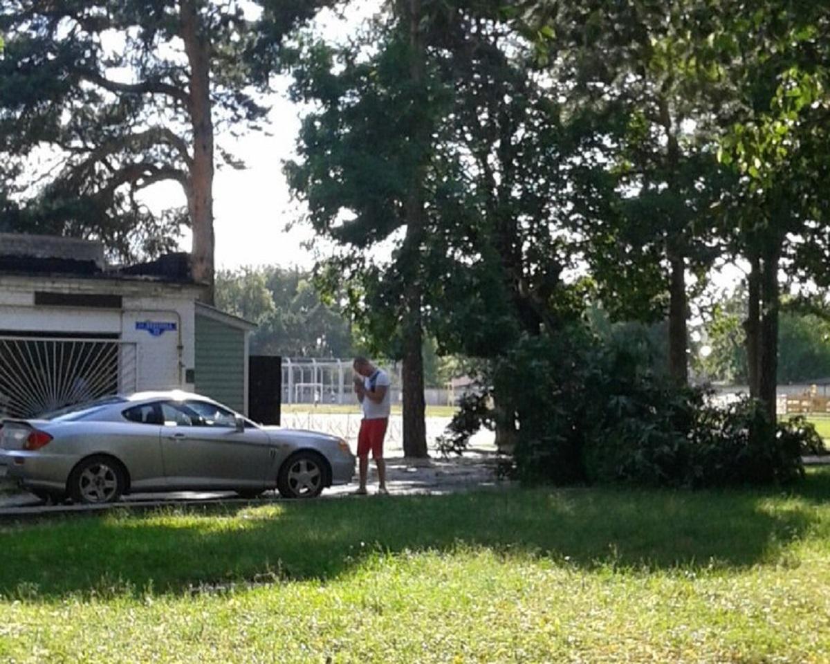 Мужчина осматривает свой пострадавший автомобиль