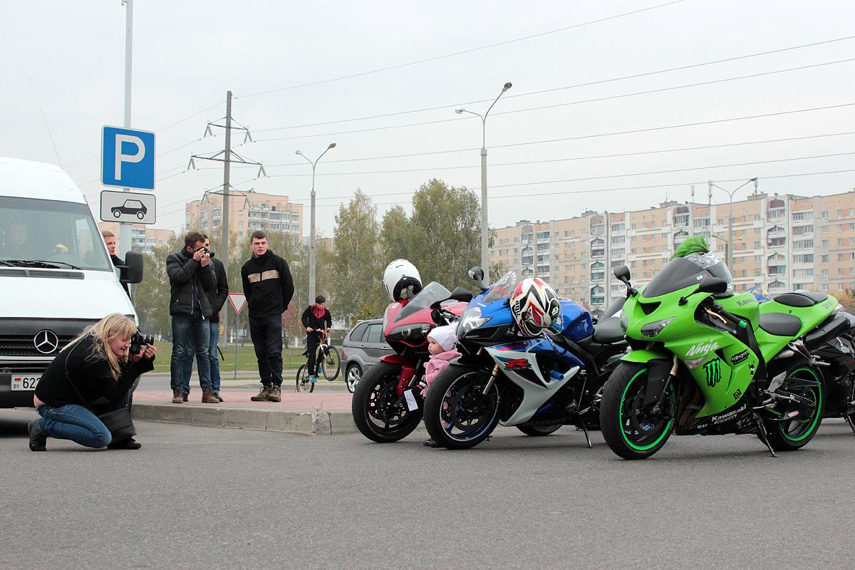 Посетители мероприятия фотографируются рядом с мотоциклами.