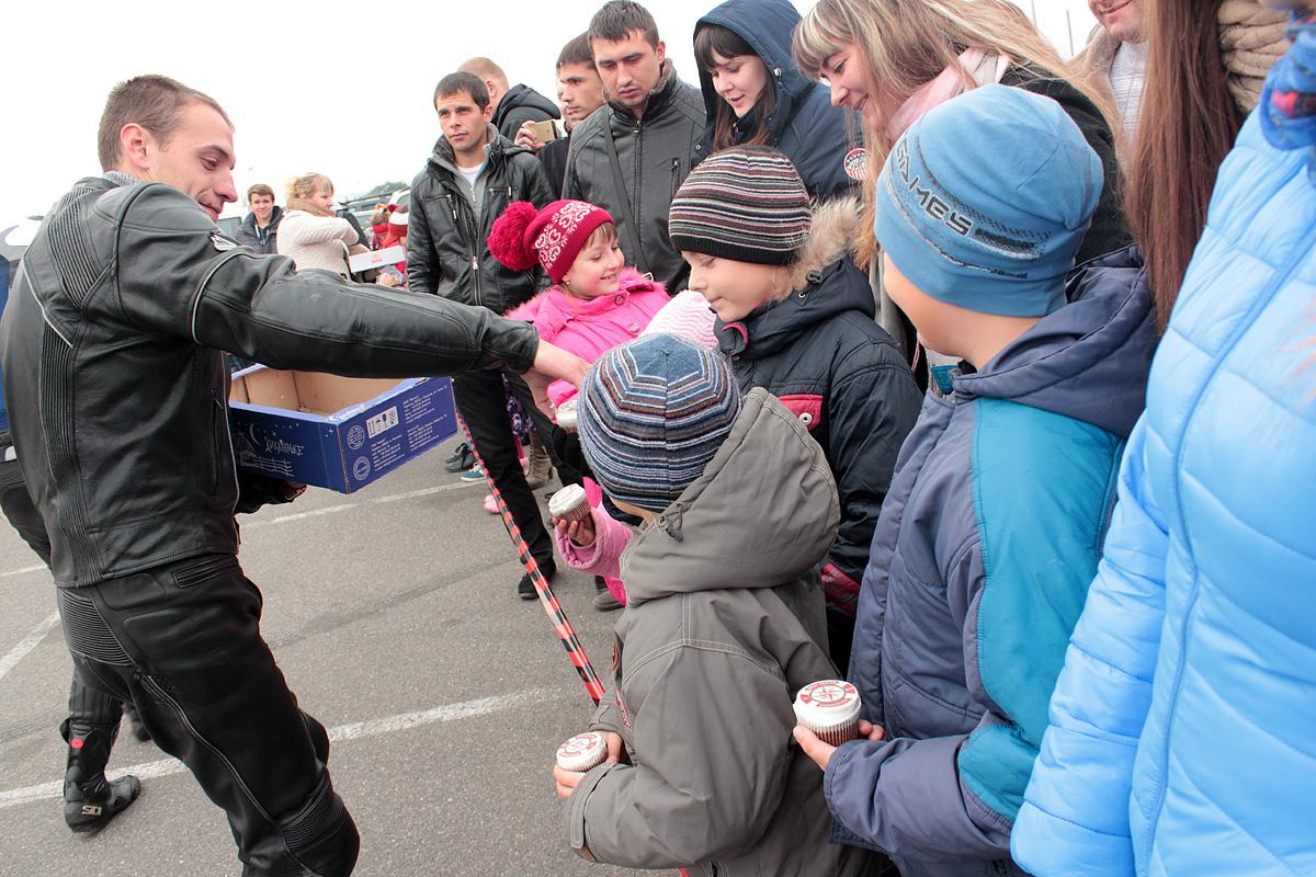 Участники мотоклуба West Region MCC угощают зрителей сладостями.