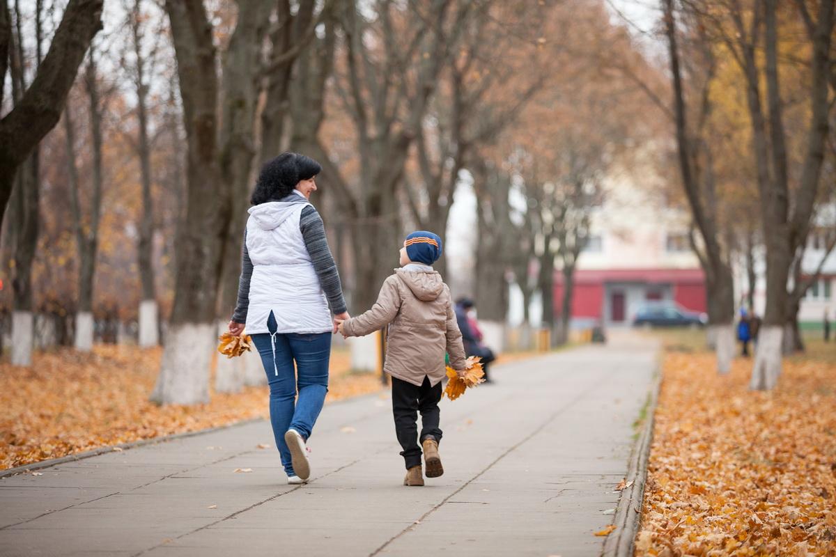 Кирилл с приемной мамой Ириной гуляют возле его новой школы. За время жизни в новой семье мальчик стал лучше учиться. Фото: Александр КОРОБ.