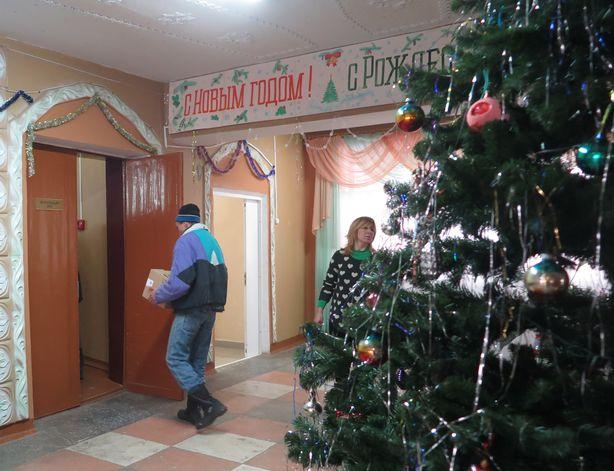 Жители Леснянского дома-интерната помогали выгружать новогодние подарки. Фото: Татьяна НЕКРАШЕВИЧ.