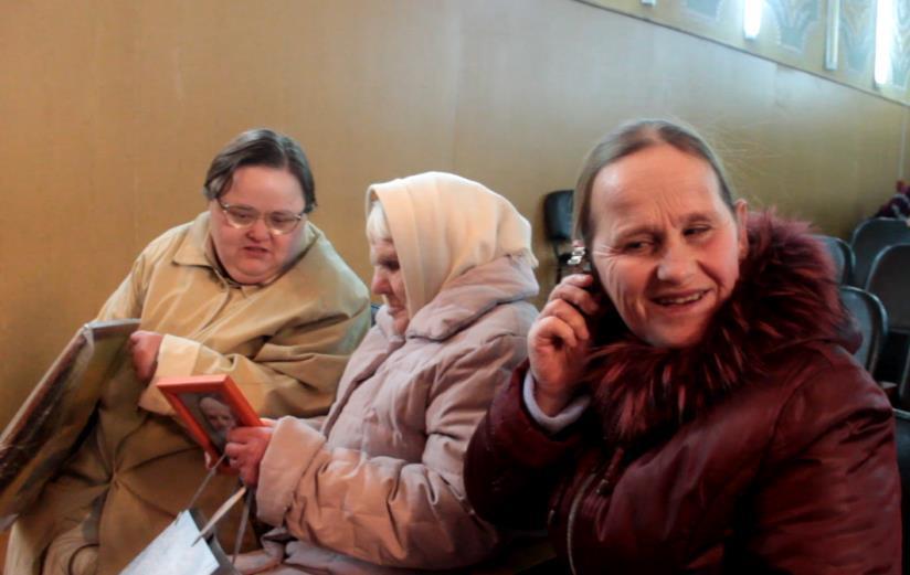 Рита Киселева слушает, как тикают ее новые часы, которые ей подарили вместо старых, сломанных. Фото: Юрий ПИВОВАРЧИК.