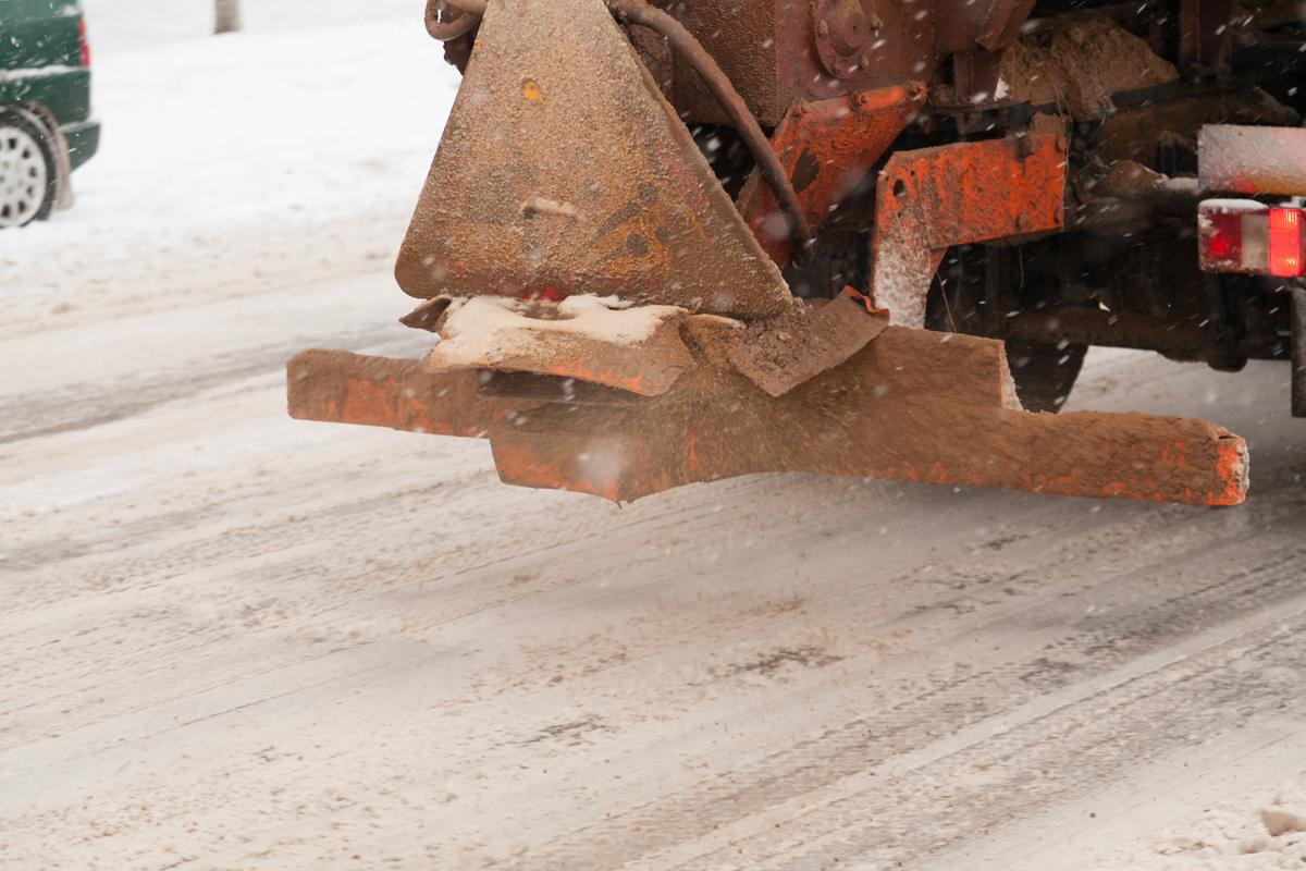 Проезжую часть дорожники очищают от снега и посыпают пескосмесью. Фото: Александр КОРОБ