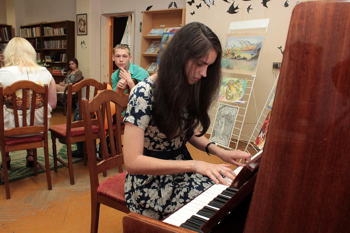Посетительница выставки Лиза исполнила несколько произведений на пианино. Фото: Юрий ПИВОВАРЧИК