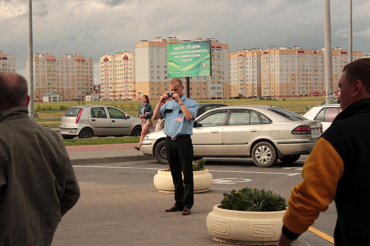 Сотрудник охраны гипермаркета «Евроопт» фотографирует проводимый пикет. Фото: Юрий ПИВОВАРЧИК