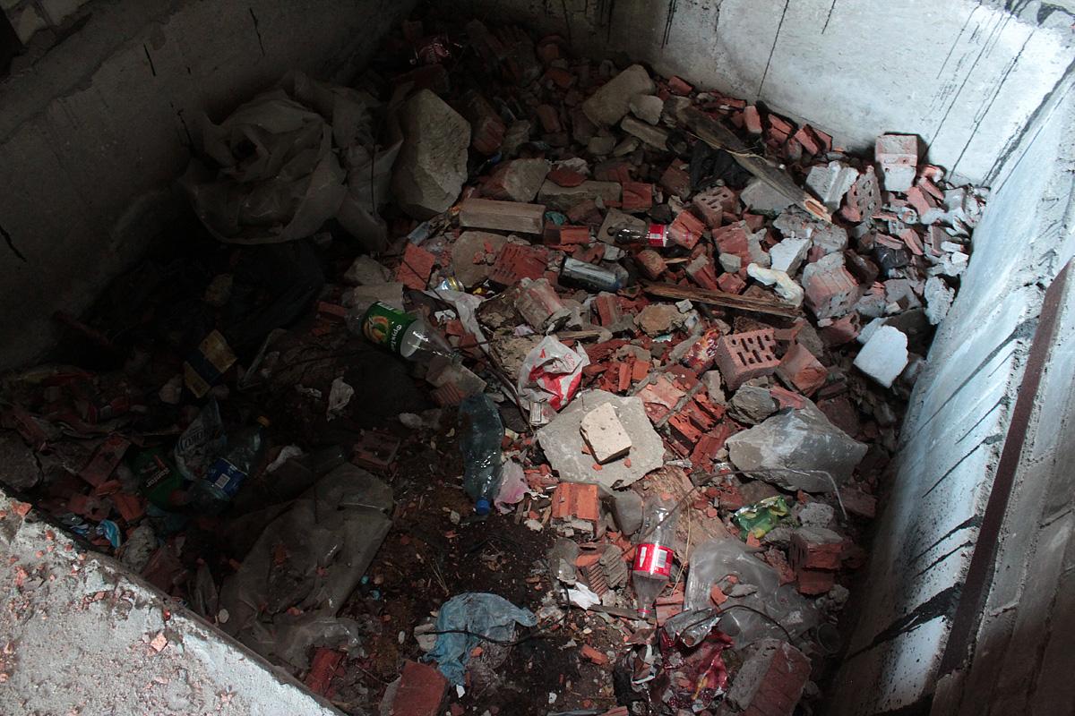 Дно шахты лифта наполнено строительным мусором. Фото: Юрий ПИВОВАРЧИК