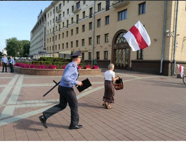 Милиционер пытается задержать участницу акции. Фото Антона Матолько
