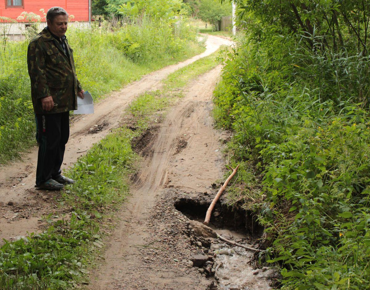 Василий Блюденов говорит, что даже в деревне по дорогам страшно ездить на автомобиле, и приводит в пример яму, которая образовалась из-за того, что ручей подмывает землю.