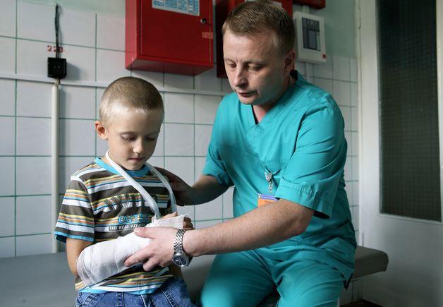 Игорь Морозов перевязывает руку 5-летнему Стасу Скомороху. Мальчик заверил, что играл на траве, споткнулся, упал и сломал руку. Фото: Евгений ТИХАНОВИЧ