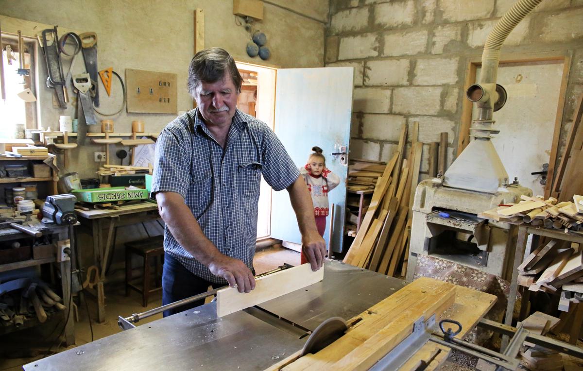 Внучка Юрия любит помогать дедушке в мастерской, но из-за сильного шума станков часто закрывает ушки. Фото: Евгений ТИХАНОВИЧ