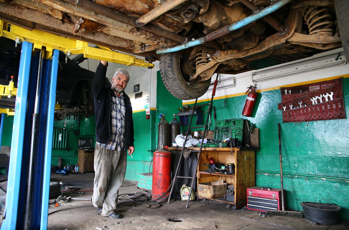 Леонид Павлюченко проверяет днище машины. Фото: Евгений ТИХАНОВИЧ