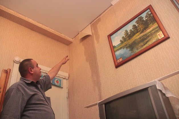 Сергей Лазукин показывает испорченные обои в детской комнате. Фото: Юрий ПИВОВАРЧИК