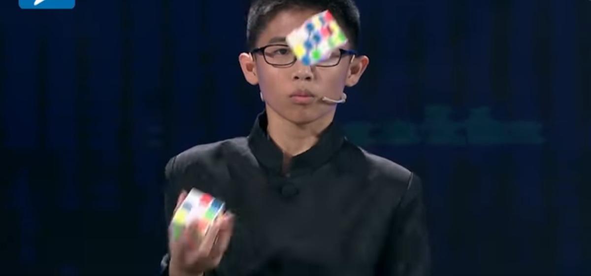 Видеофакт. Подросток собрал три кубика-Рубика, жонглируя ими