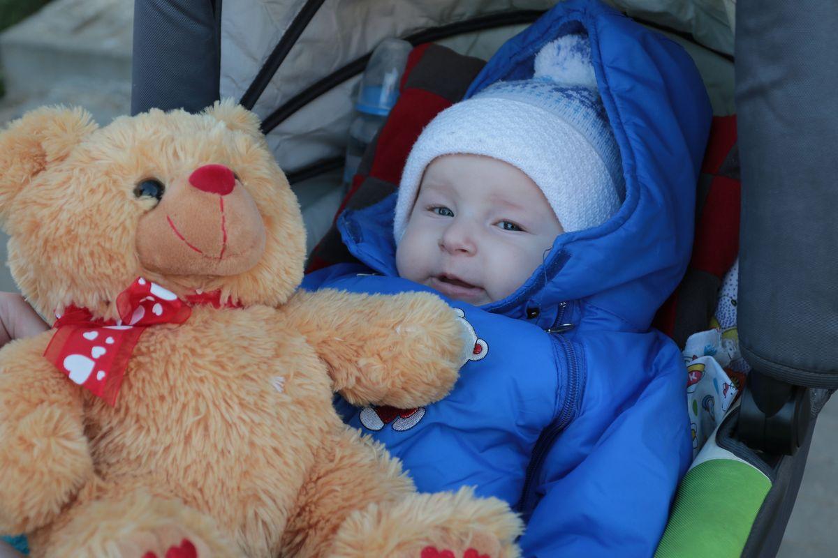 5-месячный Саша в комбинезоне, коляске и с игрушкой, которые привезли откликнувшиеся на просьбы о помощи люди. Фото: Александр ЧЕРНЫЙ
