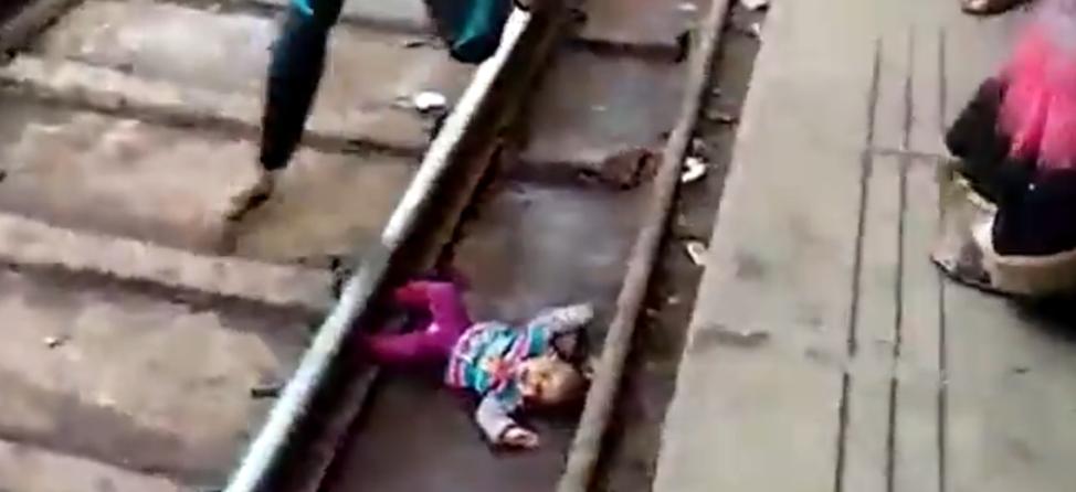 В Индии годовалая девочка выскользнула из рук матери прямо под поезд и осталась жива (видео)