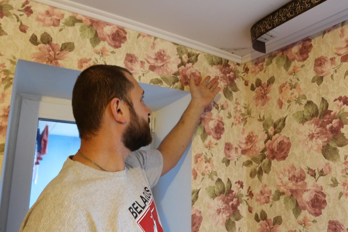 Дмитрий Банит показывает пятно плесени в своей квартире. Фото: Александр ЧЕРНЫЙ