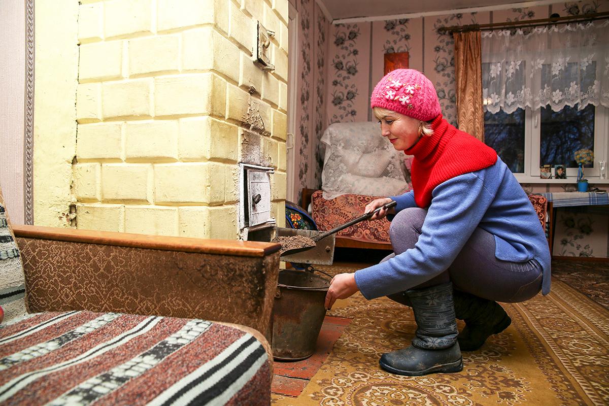 Чтобы старики не мерзли, Олеся хорошенько протапливает печь. Фото: Евгений ТИХАНОВИЧ