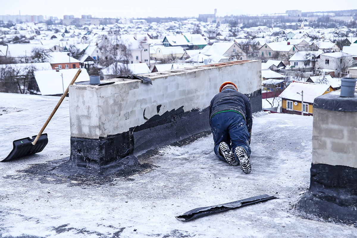 Строитель счищает снег со старой кровли крыши. Фото: Евгений ТИХАНОВИЧ